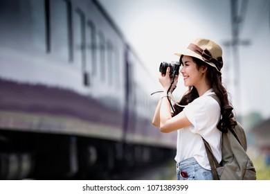 Young beautiful woman traveler with backpack holding vitage camera and taking photos a train at railway station