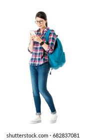 young beautiful woman traveler carrying personal luggage bag standing on white background and using mobile cell phone searching online information planning to travel.