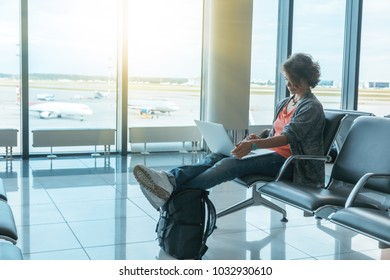 Young beautiful woman traveler sits at the airport with a laptop while waiting for her flight