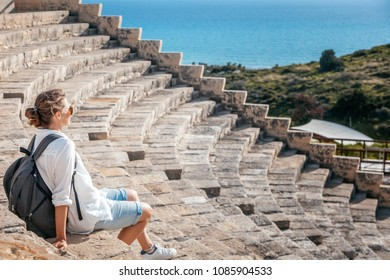 A young beautiful woman traveler sits on the steps of an amphitheater in an architectural antique museum overlooking the sea. A trip to antiquity, Cyprus, Park Kourion