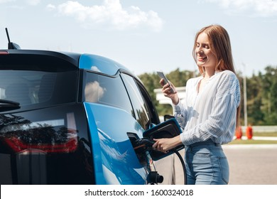 Young beautiful woman traveling by electric car having stop at charging station standing plugging cable browsing internet on smartphone smiling joyful while charing