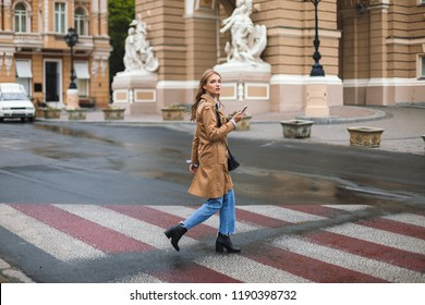 Young beautiful woman in trench coat and jeans thoughtfully looking in camera holding cellphone in hand walking on cozy city street