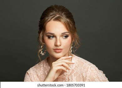Young beautiful woman with updo hairdo on dark background