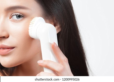 Young beautiful woman uses the apparatus for peeling. Beauty and skin care concept