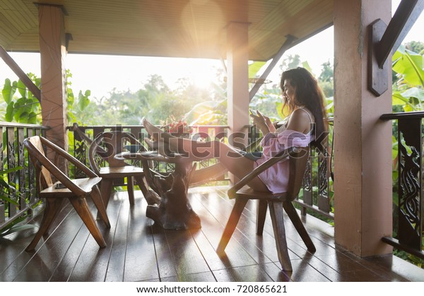 Young Beautiful Woman Using Cell Smart Phone Sit On Terrace With Tropical Forest Landscape And Morning Sun Shine Beautiful Girl Messaging Online Outdoors
