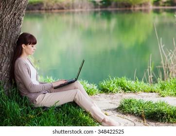 Young beautiful woman using laptop near lake
