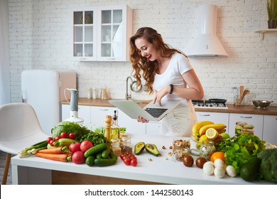 Young beautiful woman using a notebook while cooking in the modern kitchen. Healthy food and Dieting concept. Losing Weight