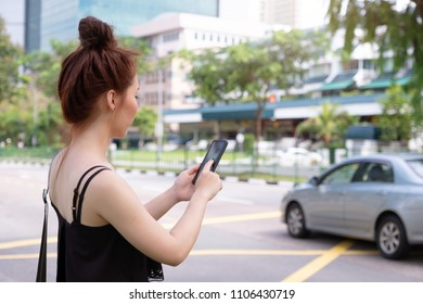 Young beautiful woman using phone to grab taxi in Singapore. Standing beside the road