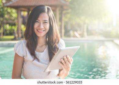 young beautiful woman using tablet while relaxing next to the pool