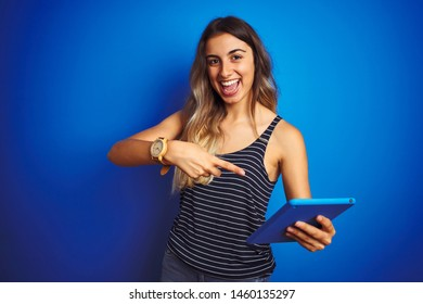Young beautiful woman using touchpad tablet over blue isolated background very happy pointing with hand and finger