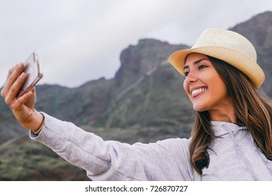 Young beautiful woman in vacation taking a selfie with her mobile smartphone camera with mountain in the background - Phone, social, addiction and travel concept