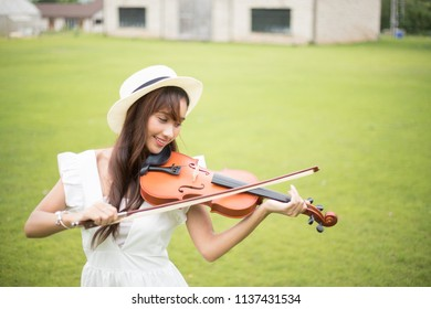 Young beautiful woman violin player in the park.