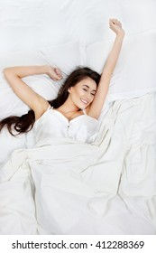 Young beautiful woman waking up in her bed fully rested. Woman stretching in bed after wake up. Healthy lifestyle.
