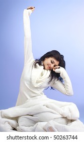 Young beautiful woman waking up over blue background