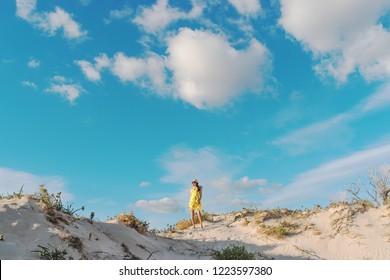 Young beautiful woman walking on a sand dune in Elafonisi beach, Crete.