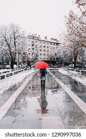 Young beautiful woman walking in the snowy cold rainy Sofia city streets near National palace of Culture in Bulgaria carrying red umbrella opened reflection in a pool of water underneath copy  space