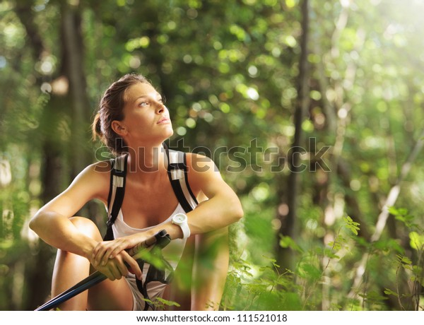 森の中に歩く棒を持つ若い美女が休憩を取る
