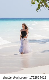 Young beautiful woman walks along the tropical beach. White sand of Ko Tachai, Thailand