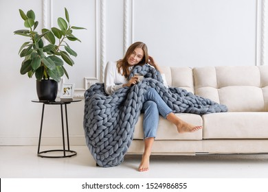 Young beautiful woman in warm chunky knitted blanket at home. Model fashion shooting. Autumn, winter season. Cozy winter style.