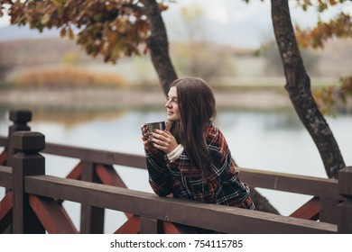 Young beautiful woman in a warm classic coat drinking tea near lake. Autumn atmosphere
