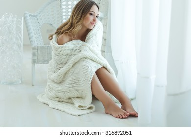 Young beautiful woman in warm knitted handmade clothes at home. Model fashion shooting. Autumn, winter season.
