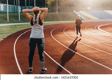 A young beautiful woman is warming up before jogging of exercising at a stadium running track.
