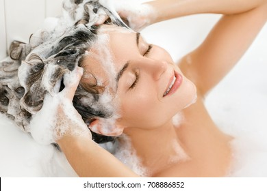 Young and beautiful woman is washing her hair with shampoo
