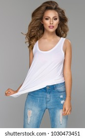 Young beautiful woman  wearin white top and jeans on grey background