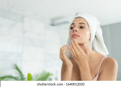 Young beautiful woman wearing bath towel and underwear standing in bathroom and looking for or squeezing acne on chin. Mirror reflection. Ugly problem teen girl skin, pimples. Skincare and beauty