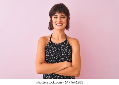 Young beautiful woman wearing black floral dress standing over isolated pink background happy face smiling with crossed arms looking at the camera. Positive person.