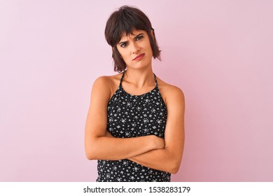 Young beautiful woman wearing black floral dress standing over isolated pink background skeptic and nervous, disapproving expression on face with crossed arms. Negative person.