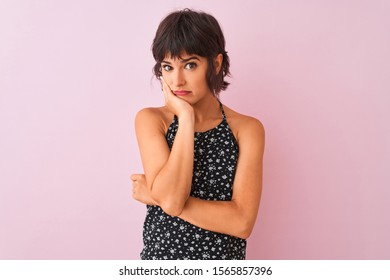 Young beautiful woman wearing black floral dress standing over isolated pink background thinking looking tired and bored with depression problems with crossed arms.