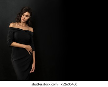 Young beautiful woman wearing black evening dress with naked shoulders posing over black background