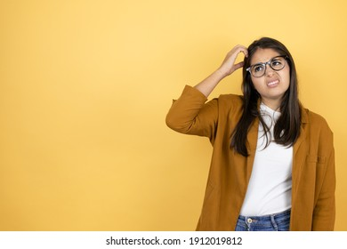 Young beautiful woman wearing a blazer over isolated yellow background confuse and wonder about question. Uncertain with doubt, thinking with hand on head