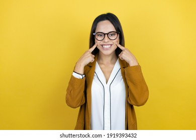 Young beautiful woman wearing a blazer over isolated yellow background smiling confident showing and pointing with fingers teeth and mouth