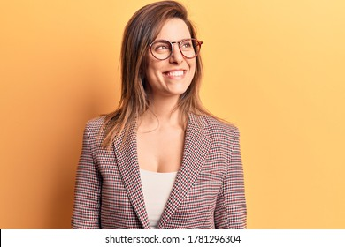 Young beautiful woman wearing business clothes and glasses looking away to side with smile on face, natural expression. laughing confident.