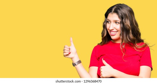 Young beautiful woman wearing casual t-shirt Looking proud, smiling doing thumbs up gesture to the side