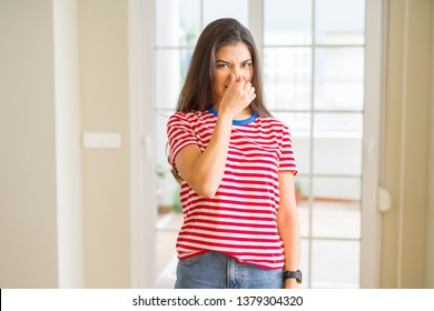Young beautiful woman wearing casual t-shirt smelling something stinky and disgusting, intolerable smell, holding breath with fingers on nose. Bad smells concept.