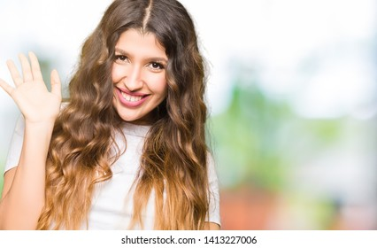 Young beautiful woman wearing casual white t-shirt Waiving saying hello happy and smiling, friendly welcome gesture