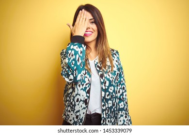 Young beautiful woman wearing casual jacket over yellow isolated background covering one eye with hand, confident smile on face and surprise emotion.
