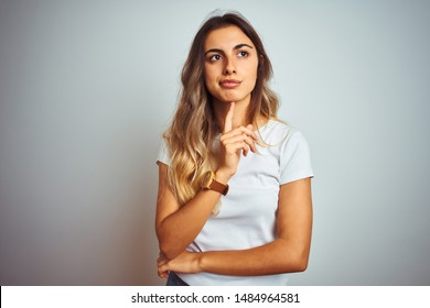Young beautiful woman wearing casual white t-shirt over isolated background Thinking concentrated about doubt with finger on chin and looking up wondering