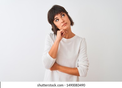 Young beautiful woman wearing casual t-shirt standing over isolated white background with hand on chin thinking about question, pensive expression. Smiling with thoughtful face. Doubt concept.