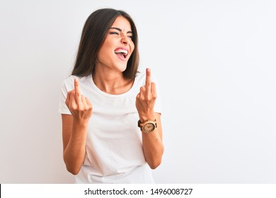 Young beautiful woman wearing casual t-shirt standing over isolated white background Showing middle finger doing fuck you bad expression, provocation and rude attitude. Screaming excited