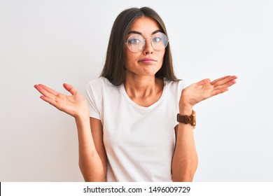 Young beautiful woman wearing casual t-shirt and glasses over isolated white background clueless and confused expression with arms and hands raised. Doubt concept.