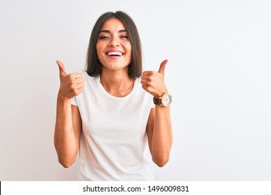 Young beautiful woman wearing casual t-shirt standing over isolated white background success sign doing positive gesture with hand, thumbs up smiling and happy. Cheerful expression and winner gesture.
