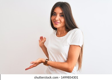 Young beautiful woman wearing casual t-shirt standing over isolated white background Inviting to enter smiling natural with open hand