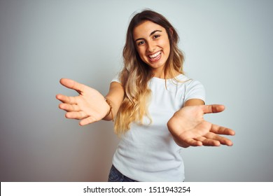 Young beautiful woman wearing casual white t-shirt over isolated background smiling cheerful offering hands giving assistance and acceptance.