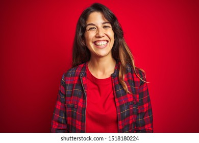 Young beautiful woman wearing casual jacket standing over red isolated background Shouting frustrated with rage, hands trying to strangle, yelling mad