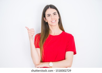 Young beautiful woman wearing casual red t-shirt over white isolated background smiling with happy face looking and pointing to the side with thumb up.