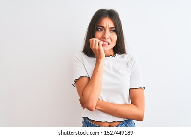 Young beautiful woman wearing casual t-shirt standing over isolated white background looking stressed and nervous with hands on mouth biting nails. Anxiety problem.